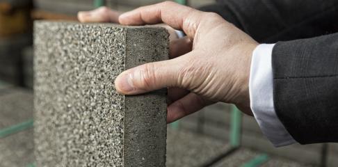 Sfeerimpressie: twee handen op een betontegel